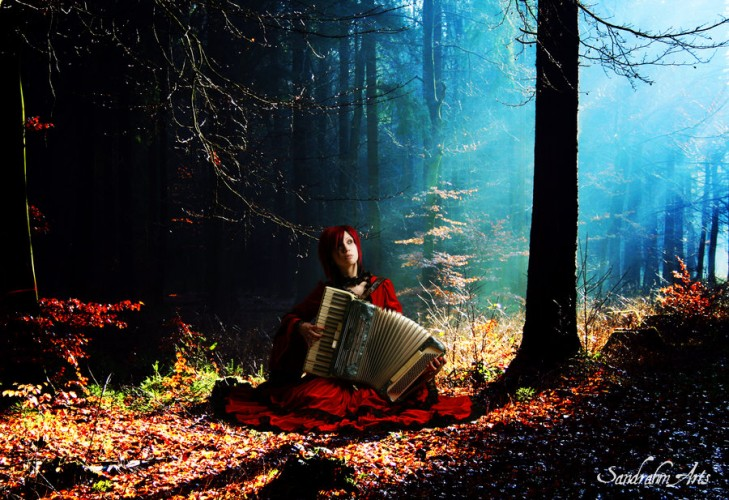 woman playing accordion in forest
